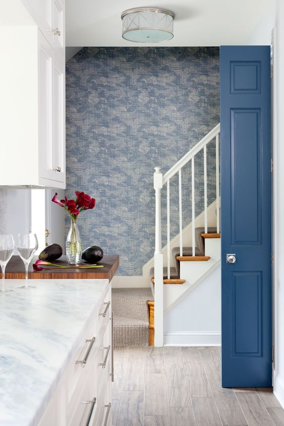 Detail of a wallcovering ascending staircase and a blue door. Blue and White Classic Decor Inspiration: Ella Scott Design. #blueandwhite #classicdecor #interiordesignideas #interiordesigninspiration #traditionalstyle