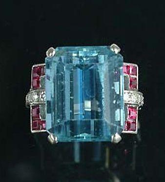 An art deco aquamarine dress ring, circa 1930,  the rectangular step-cut aquamarine, to stirrup-shaped calibré-cut ruby and single-cut diamond shoulders