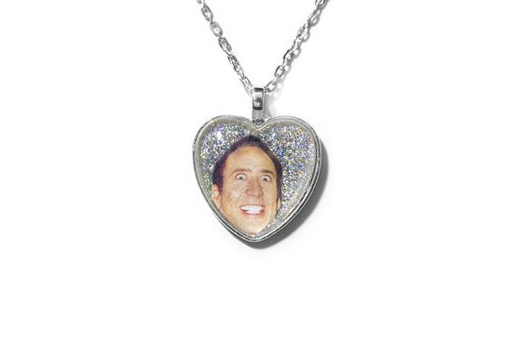 """""""I am not a demon. I am a lizard, a shark, a heat-seeking panther. I want  to be Bob Denver on acid playing the accordion."""" -Good ol' Nic Cage  This necklace is handmade to order. It features a 1"""" glass cabochon on top  of Nicolas Cage's face and a holographic silver glitter background. The  glass is set in a silver-plated pendant. It comes with a 16"""" silver-plated  chain.  Please read: This is item is handmade to order. Due to the volume of orders  we receive, handmade items may take up to…"""