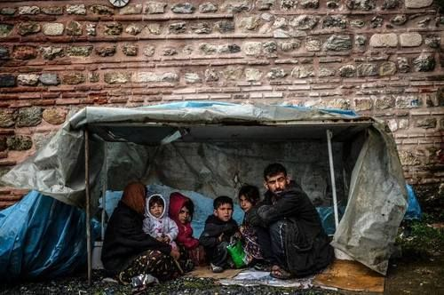 A Syrian refugee family from Aleppo stay under a shelter during a rainy day on March 8, 2014, in the Uskudar district of Istanbul