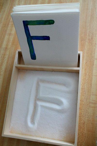 Casillero hecho con cartón en el cual los niños pueden practicar las letras haciendo una copia en el azúcar o arena de lo que ven en la ficha de enfrente.