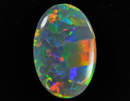 Black Opal - colors arise in opal when there is uniformity in the size of silica spheres.  Patches of different size spheres (while still uniform to neighbors) results in the multi-color pattern seen here.