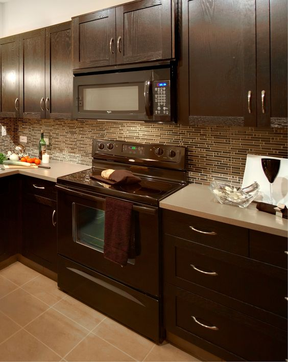 Modern kitchen with glass mosaic backsplash taupe floor for Brown kitchen cabinets with black appliances