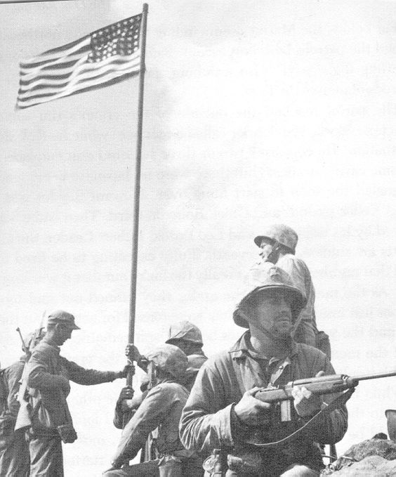 The first flagraising atop Mount Suribachi, February 23, 1945. Hank Hansen (without helmet), Boots Thomas (seated), John Bradley (behind Thomas) Phil Ward (hand visible grasping pole), Jim Michaels (with carbine) and Chuck Lindberg (behind Michaels). Photo by Lou Lowery. 10AM, Feb. 23, 1945