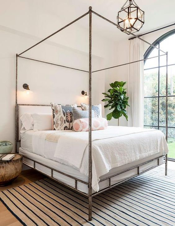 Chic bedroom features a metal canopy bed, Oly Studio Marco Bed, dressed in soft white bedding and pink and gray ikat pillows as well as a pink ikat bolster pillow placed atop a beige and navy striped rug illuminated by glass vintage barn wall sconces and a Suzanne Kasler Morris Lantern.: