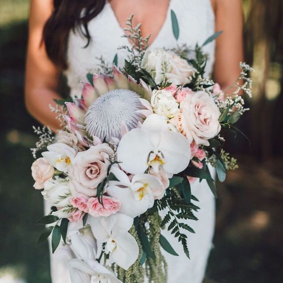 A Unqiue Tropical Wedding Bouquet With King Proteas Blush And Mauve Roses Greenery And Tropical Wedding Bouquets White Orchid Bouquet Orchid Bouquet Wedding