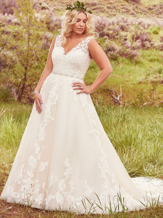 Maggie Sottero - SYBIL, This exquisite ball gown plus size wedding dress is complete with floral lace appliques drifting down a tulle skirt, an elegant illusion V-neckline, and a glittering Swarovski crystal belt. Finished with plunging V-back and crystal buttons over zipper closure.
