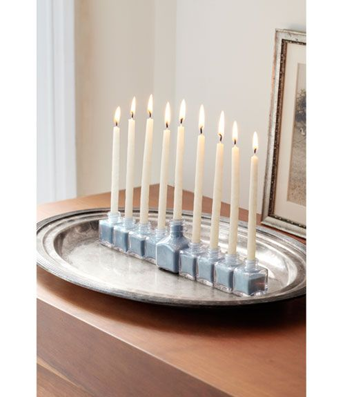 A Menorah made from salt and pepper shakers (small bottles) and one large one (all from The Container Store) and filled with blue sand.