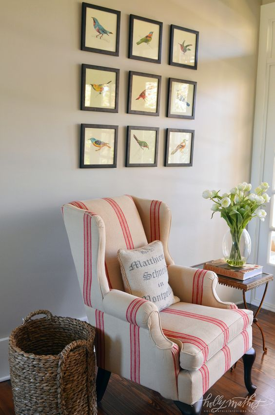 Traditional decor and country style in a sitting area of a Louisiana Farmhouse with red stripe grainsack wing chair. Framed bird prints decorate the wall of this sweetly inspiring space by Holly Mathis Interiors. #traditionaldecor #countrydecor #wingchair #redstripes #grainsack