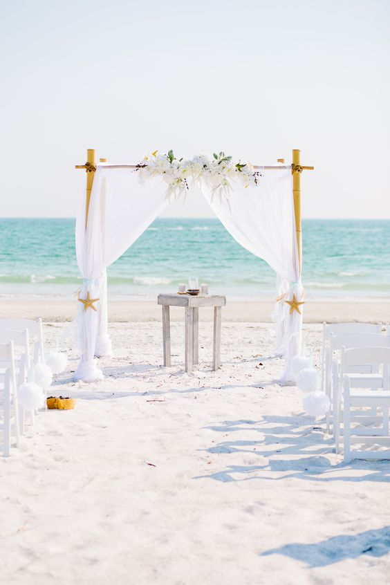Elegant white beach wedding arbor.