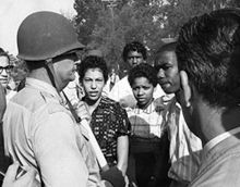 On September 4, 1957 Governor Orville Faubus deployed the Arkansas National Guard to prevent nine African American students (the Little Rock Nine) from entering Central High in Little Rock.  Three weeks later President Eisenhower sent the 101st Airborne and nationalized the state National Guard to facilitate their entry. In this photo by Will Counts, Lt. Col. Marion Johnson, commander of National Guard troops, turns back Carlotta Walls and other students.