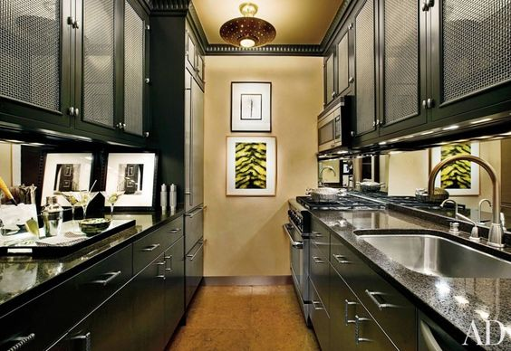 The galley kitchen in designer Arthur Dunnam's Manhattan apartment features a mirrored backsplash.