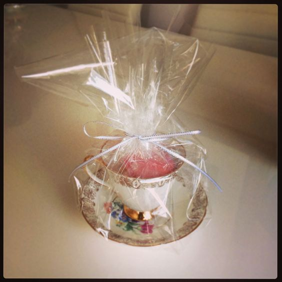 Party favours. Vintage teacups filled with macaroons wrapped in cellophane.