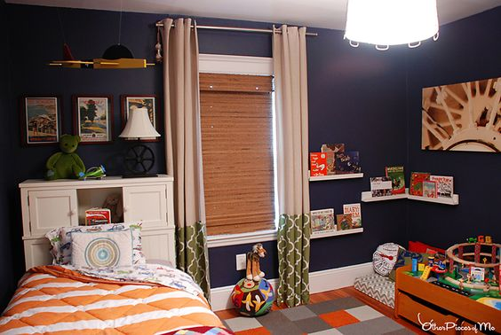 Love the navy walls and orange accents in this #bigboyroom!