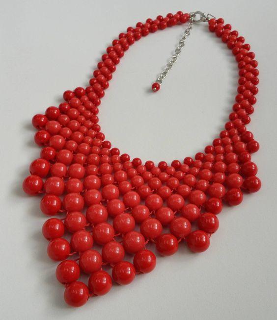 Maxi colar confeccionado com bolas de resina em vermelho e coral. Acabamentos em metal niquelado. <br>Comprimento( colar aberto) :41 cm + 7 cm de corrente extensora <br>Altura meio do colar: 9 cm