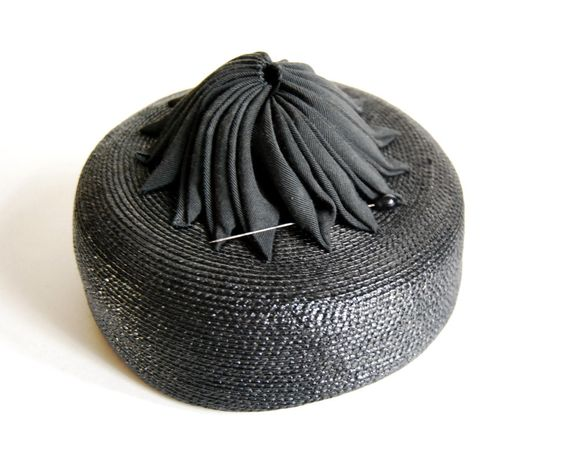 1960's black straw pillbox hat with glass hatpin | Labels: Jan Leslie Custom Design, Stix Baer & Fuller French Room (a now defunct St. Louis department store) | This fun little vintage hat  is made of black synthetic straw and has cocarde, or cockade of ribbon, on top. The ribbon is folded into a mounded swirl, centered on the top of the hat