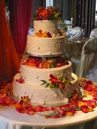 Traditional style wedding cake with autumn color fresh flowers and petals.