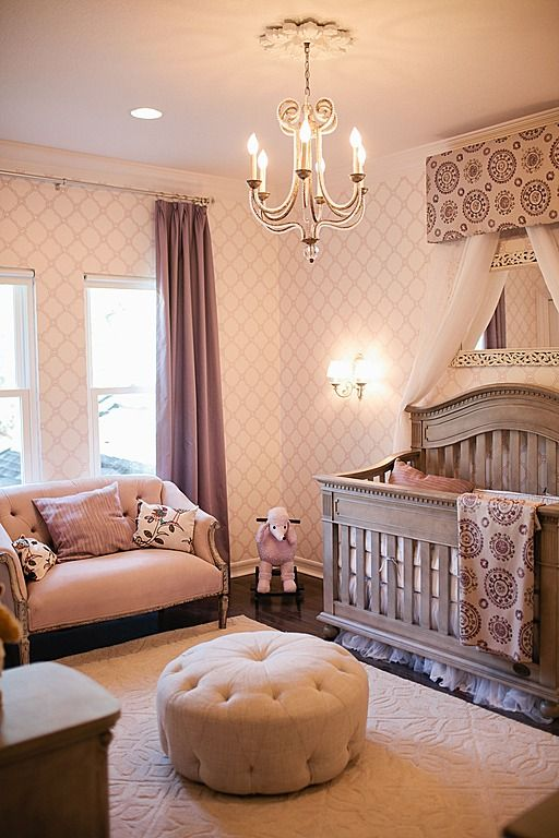 This nursery features a subtly ornate style, courtesy of patterned wall covering, carved wood and button tufted love seat and circular ottoman, and immense natural carved wood crib. Wall sconce and chandelier light the space.: