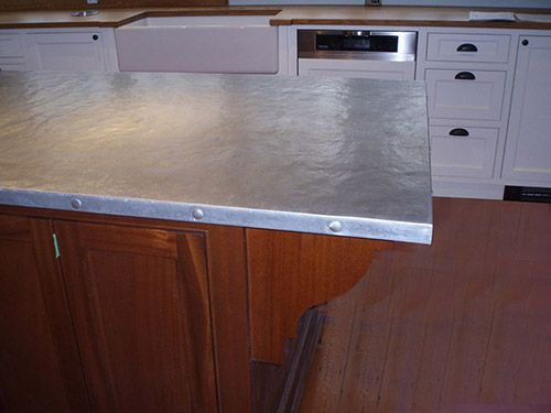 Hand Hammered zinc kitchen island countertop, rivets on edge.
