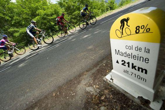 Los ciclistas pasan por el poste que indica la inclinación del Col de la Madeleine durante la 11ª etapa