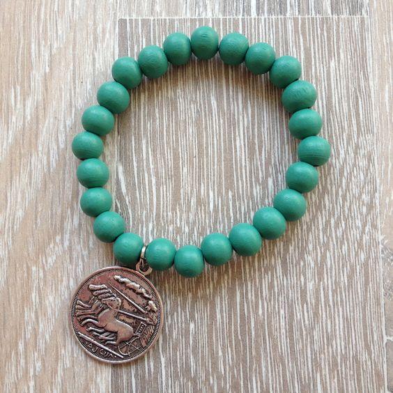 Armband van 8mm winter green hout met metalen Romeinse munt. Van JuudsBoetiek, €3,50. Te bestellen op www.juudsboetiek.nl.