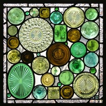 Creative mosaic using serving plates, wine bottle bottoms, stemware bottoms and faceted stained glass jewels.