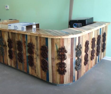 Bar with rounded corner created from pallet wood and adorned with salvaged scroll work from old iron fencing.