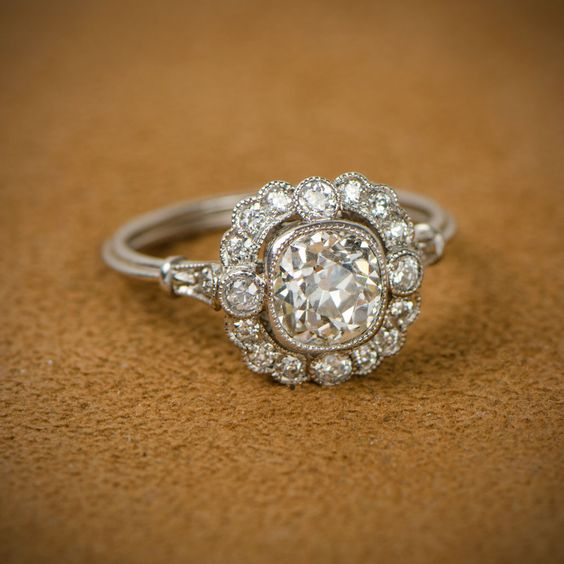 A stunning vintage cushion cut diamond engagement ring, set in platinum and adorned with a halo of diamonds.