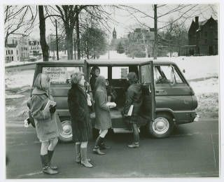 "Students in line at ""4 College Transportation Service"" van on a winter day, with view north up College Street toward Mary Lyon Hall in the distance :: Archives & Special Collections :: circa 1968"