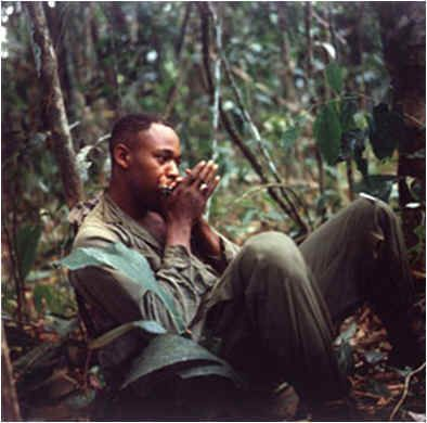 PFC Frank Williams, Combat Engineer, 173rdENGR BN, 173rdABN BDE, plays his harmonica during a lull in the operations at Dak To, 26 November 1967. U. S. Army photograph, National Archives.