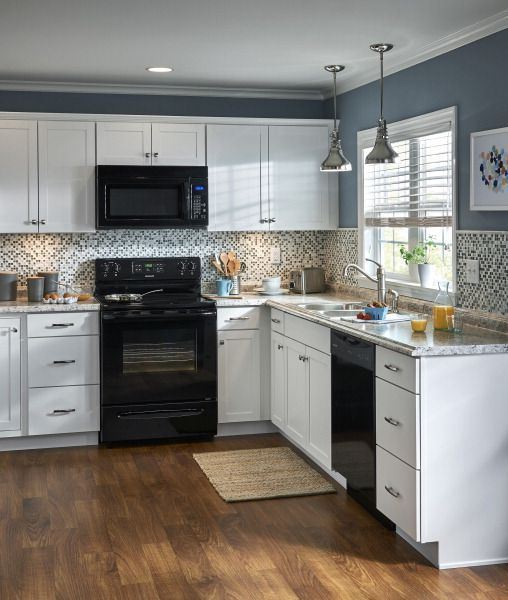 White Cabinetry And A Mosaic Tile Backsplash Contrast With Black Appliances And A Blue Gray Wall Color Black Appliances Kitchen Stock Cabinets Kitchen Cabinets