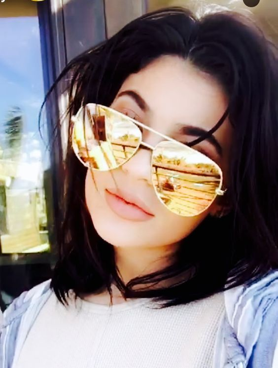 Kylie wearing Quay Australia x Desi High Key gold sunglasses