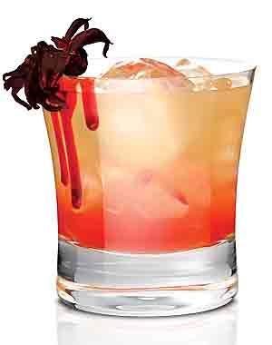 Coctel The Spidey 2 onzas de Skyy Vodka 1 cucharada de jarabe de frutos de pasión ½ onza de jugo de naranja ½ onza de jugo de piña 1 flor de jamaica para decorar  Para el jarabe de frutos de pasión 2 lichis ½ cucharada de azúcar