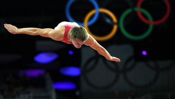 Dmitry Ushakov lors de la finale de trampoline, aux Jeux olympiques de Londres en 2012. Il monte sur la deuxième place du podium, derrière le ChinoisDong Dong et devantLu Chunlong.
