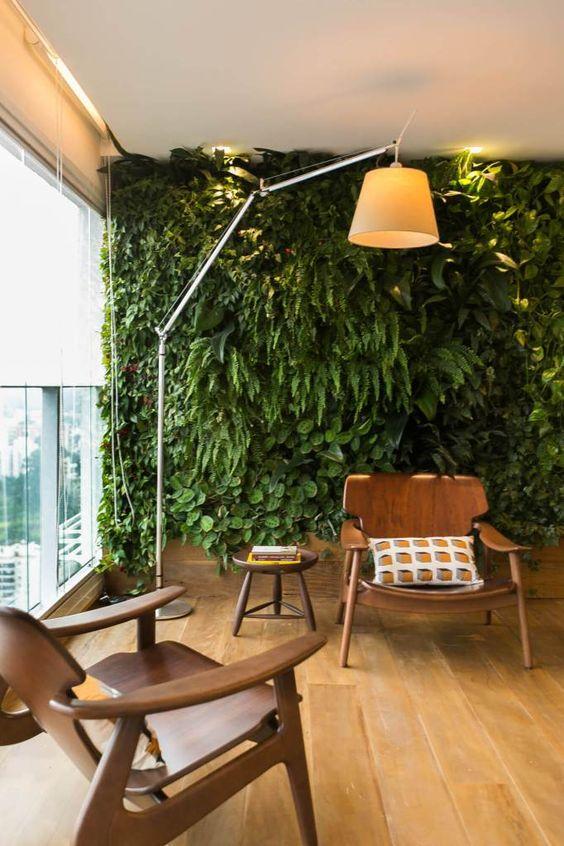 Jardim vertical em sacada, com varias samambaias e outras plantas, imagem com luminária de piso e poltrona. Jardim Vertical: A Natureza nas Cidades projeto por Fa.Z Arquitetura no Panamby