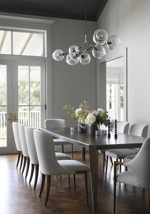 Ten Sleek Gray Dining Chairs Surround A Brown Wood Dining Table