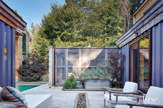 For a new take on the classic screened-in porch, Fredman stripped the walls off two shipping containers, joined them at the base, added wooden support columns and wrapped them with steel mesh. Bleu Nature chairs and a built-in bench surround a dry rock bed. The Zen-inspired landscaping softens the structure's industrial edge.: