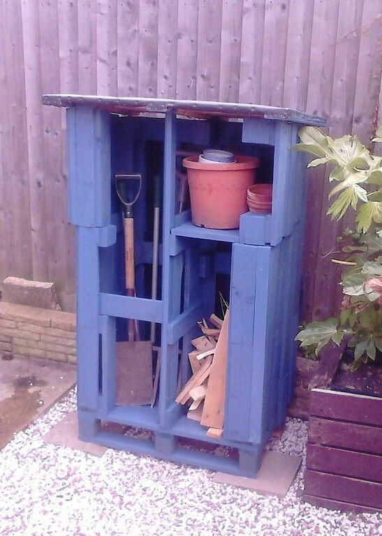 Woodshed made from pallets, with a little potting shelf