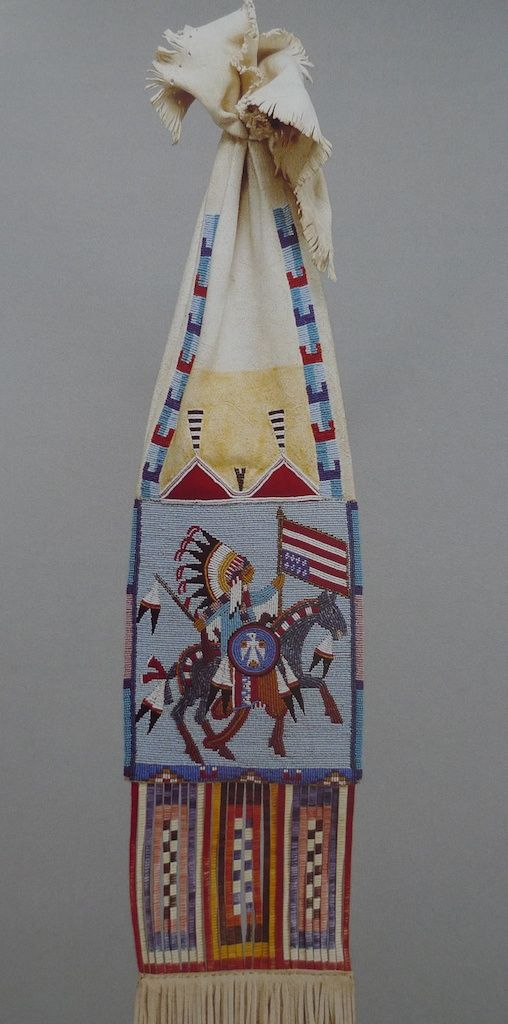 Joyce Growing Thunder Fogarty,  Arizona 1977. Tobacco bag. The subject matter is more ironic than it appears. A warrior is shown parading in the tradition of victory dancing. The warrior in full regalia, decorated with eagle feathers, while the horse prances with pride, but the American flag is displayed up side down. An international signal of distress adopted by the American Indian Movement as an emblem of protest. This was Joyce's personal statement of protest.