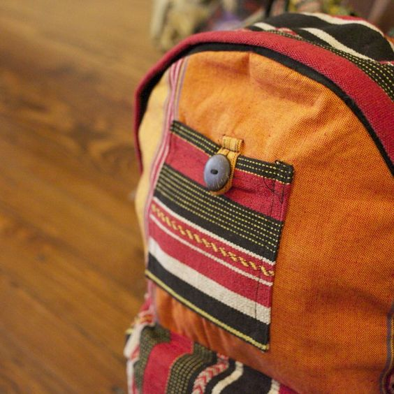 This colorful striped cotton backpack is accented with gheri fabric. It features multi colored adjustable straps and a hanging hook as well as two front pockets. The main pocket and large front pocket both have a zipper closure, and the smaller front pock