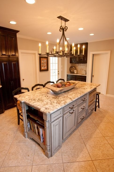 Large rustic chandeliers within over white marble top Large kitchen islands with seating and storage