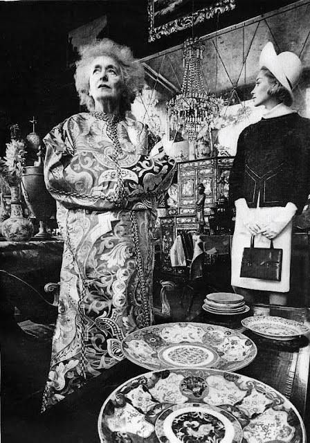 """Rose Cumming * in her antiques shop, 1964 by Jeanloup Sieff for Harper's Bazaar. Upon arriving in New York from a sheep ranch in her native Australia in 1917, she sought career advice from her friend Frank Crowninshield, the editor of Vanity Fair, who asked if she wanted to be a decorator. """"Perhaps I would, but first tell me what it is,"""" she said.  Rapidly, however, she began to develop her idiosyncratic style."""