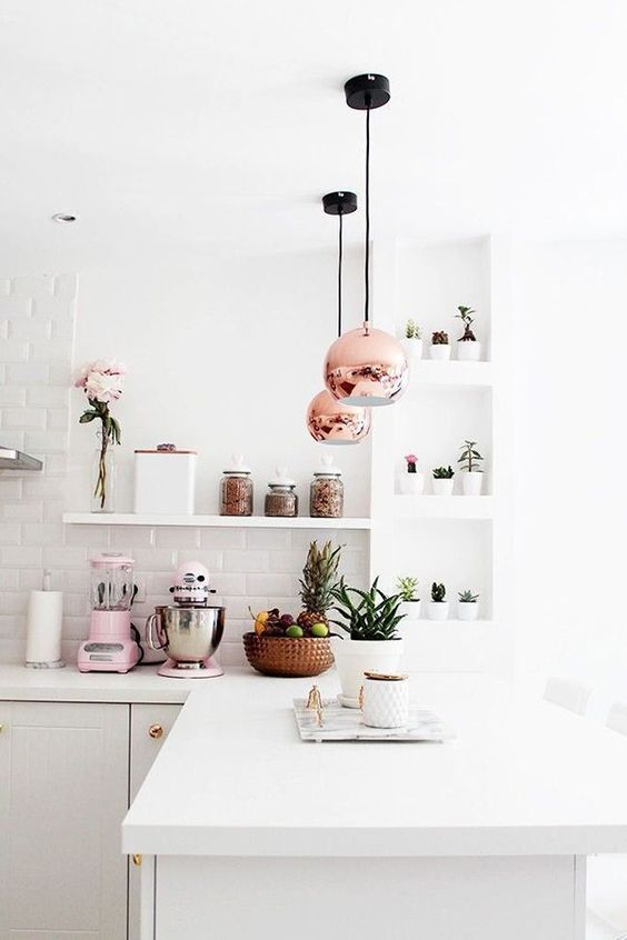 All white kitchen with carrara marble counter tops, copper fixtures, lights, pots and pans, and pink fresh flowers and a candle on the side. Friday Favorites / Lauren Conrad | Bloglovin'