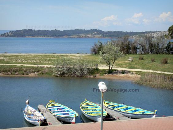 Gruissan: Boats moored in foreground with a view of the end of the pond wood, the Gruissan pond and the surrounding green landscape; in the Regional Natural Park of Narbonne in the Mediterranean - France-Voyage.com