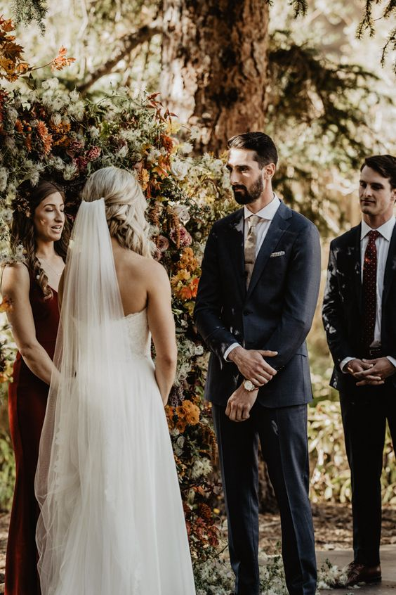 This groom wore a non-traditional navy suit + gold tie for his foresty wedding   Image by We are Matt and Jess