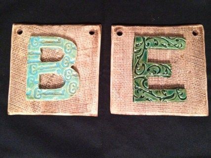 """These are two ore customized tile with a burlap imprint on the tile.  The """"B"""" has a key stamping; the """"E"""" has a flourished stamping.  All of the stamping and patterns are done before the bisque firing.  Orders yours at www.hippyandpreppy.com"""