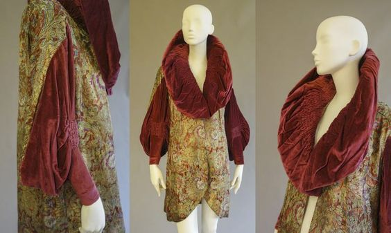 Lot No. 150 Auction April 1st, 2015 A coat, 1920s, gold silk brocade with floral decoration, burgundy silk velvet, salmon silk lining (fragile), sleeves and shawl collar with elaborately smocked parts.