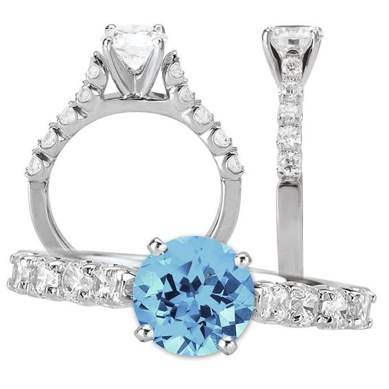 This simply gorgeous 18k white gold simulated aquamarine engagement ring features a fabulous 6.5mm round Chatham gem quality simulated aquamarine center stone. The diamond-studded shank is adorned with 10 G-H color eye-clean SI1-SI2 clarity natural diamond accents weighing an eye-catching 0.44 cttw. The shank measures 2.3mm wide and curves into a 6mm high cathedral. This lovely engagement ring coordinates with diamond wedding band KI-117053-W, sold separately.