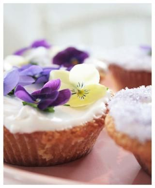 sweet muffins with icing and edible flowers