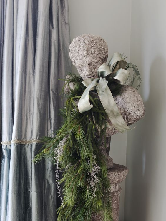 Moss and garland trimmings from the banister adorn a cement statue in the dining room. Do this with my lady statue in dining room.